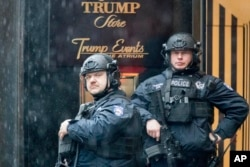FILE - Heavily armed police officers stand guard in the rain outside Trump Tower in New York, Nov. 29, 2016.