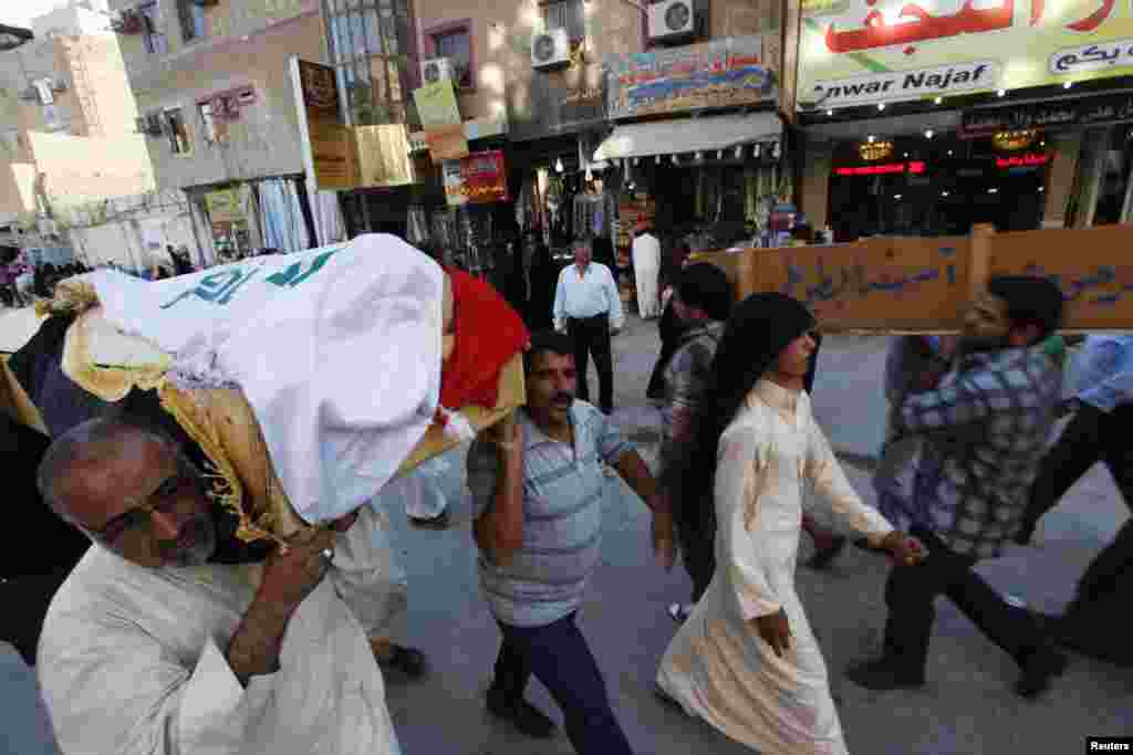 Mourners carry the coffin of a police officer who was killed in a Basra car bomb attack during a funeral in Najaf, Iraq, June 16, 2013.