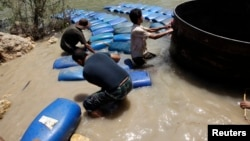 A group of men smuggle diesel fuel from Syria to Turkey hoping to sell it at a higher price, across the al-Assi River in Darkush town, Idlib, May 26, 2013.