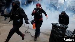 Các nhà hoạt động đang chạy thoát khỏi lựu đạn gây choáng của cảnh sát khi cuộc biểu tình chống ông Trump trong ngày nhậm chức trở nên bạo động.