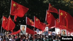 Demonstrators holding posters of China's late Chairman Mao Zedong, Chinese national flags and banners march past riot policemen during a protest on the 81st anniversary of Japan's invasion of China, outside the Japanese embassy in Beijing, September 18, 2