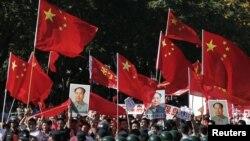 中国示威者手举毛泽东象、国旗和标语在北京日本使馆外抗议游行