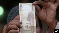 Người bán hàng Ấn Độ kiểm tra tính xác thực của tờ 500 rupee tại một khu chợ ở Ahmadabad.