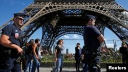 Des policiers français patrouillent autour de la Tour Eiffel à Paris, le 20 août 2016.