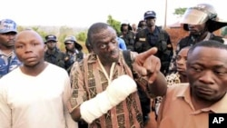 Uganda's Forum for Democratic Change (FDC) leader Kizza Besigye (C) argues with police before his arrest at the Kasangati suburb of the capital Kampala, April 18, 2011. Ugandan opposition leader Besigye was arrested on Monday during a protest against high