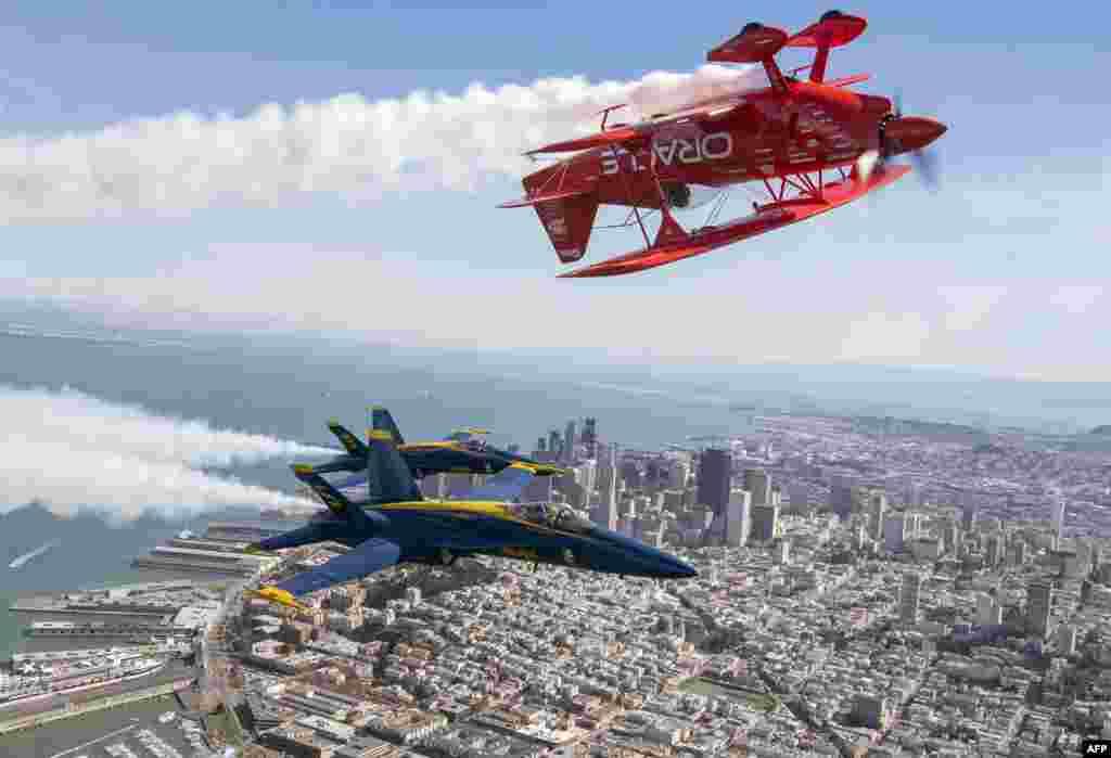 Pesawat Blue Angels nomor 5 dan 6 milik Angkatan Laut AS terbang di bawah pesawat Oracle Challenger III yang diterbangkan pilot Sean Tucker di atas San Francisco, California sebagai bagian dari latihan untuk Pekan Armada (6/12). (AFP/Josh Edelson)