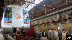Delhi Metro officials tour metro train facility in New Delhi, Sept. 17, 2002.