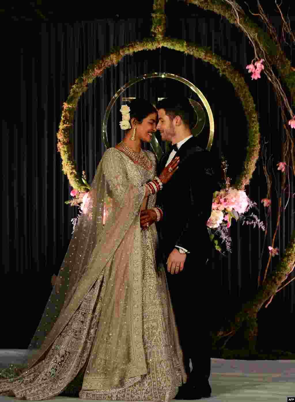 Aktris Bollywood Priyanka Chopra (36 tahun/kiri) dan musisi AS Nick Jonas (26 tahun), yang baru saja menikah, berpose untuk foto saat resepsi di New Delhi, India.