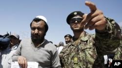 Binh sĩ Afghanistan (phải) bên cạnh một tù nhân vừa được trả tự do từ nhà tù Bagram ở phía bắc thủ đô Kabul, ngày 10/9/2012