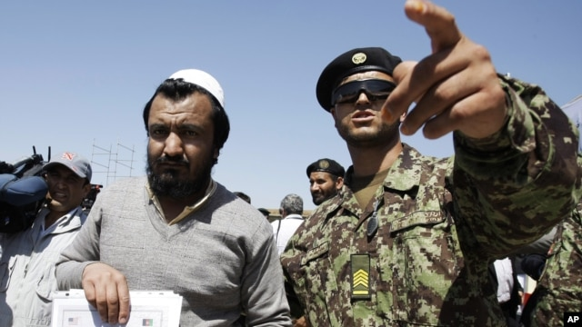 An Afghan soldier, right, escorts a released prisoner, Mohammad Karim, following a hand over ceremony of U.S.- run prison to Afghan government in Bagram north of Kabul, Afghanistan, Sept. 10, 2012.