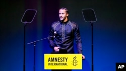 Former NFL quarterback and social justice activist Colin Kaepernick speeches after receiving the Amnesty International Ambassador of Conscience Award for 2018 in Amsterdam, Saturday April 21, 2018. Kaepernick became a controversial figure when refusing to stand for the national anthem, instead he knelt to protest racial inequality and police brutality.
