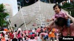 Seorang balita bermain bermain saat berlangsung festival tahunan Pink Dot yang diadakan di Hong Lim Park, Singapura, 28 Juni 2014. Pink Dot diadakan untuk mengkampanyekan penerimaan komunitas LGBT (lesbian, gay, biseksual dan transgender) di Singapura.