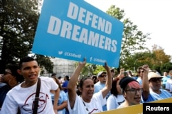 A woman holds a sign during a rally calling for the passage of a clean Dream Act outside the U.S. Capitol in Washington, Sept. 26, 2017.