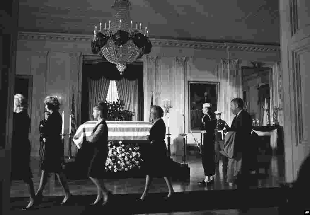 Members of the White House staff file past the body of John F. Kennedy, lying in repose in a closed, flag-draped coffin in the historic East Room of the Executive Mansion in Washington, Nov. 23, 1963.