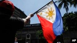 Tư liệu: Một người biểu tình vẫy cờ Philippines tại cuộc tuần hành bên ngoài Bộ Ngoại giao ở Manila, 21/6/2019. TT Duterte gọi vụ tàu TQ đâm chìm một tàu cá Philippines là một 'tai nạn nhỏ.' 22 ngư phủ Philippines được tàu cá Việt Nam cứu vớt. (AP Photo/Aaron Favilla)