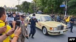 Police escort the limousine carrying Thailand's Queen Suthida and Prince Dipangkorn Rasmijoti as royalist supporters take photos of the the royal motorcade in Bangkok on October 14, 2020. (Photo by Mladen ANTONOV / AFP)