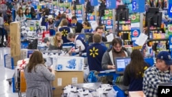 FILE - Sales clerks ring up customers at a Walmart store in Bentonville, Arkansas, Nov. 27, 2014. New data shows that, in a trend reversal, Americans enjoyed a median household income hike of 5.2 percent in 2015.