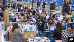 Sales clerks ring up customers at Walmart in Bentonville, Arkansas, Nov. 27, 2014.