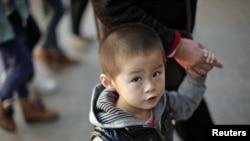 Seorang anak berjalan bersama neneknya di sebuah area perbelanjaan di pusat kota Shanghai (28/11). Pemerintah Tiongkok tengah mengkaji ulang kebijakan satu anak yang kontroversial.