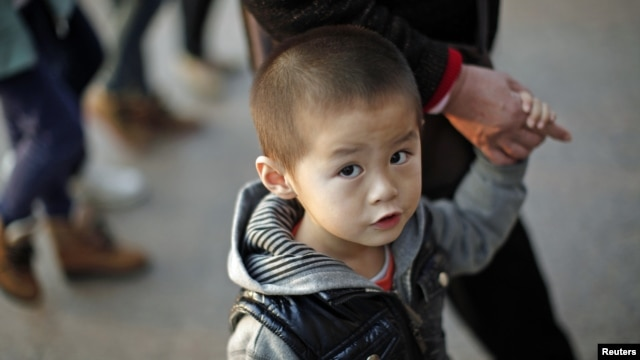 A boy walks with his grandmother at a commercial area of downtown Shanghai, November 28, 2012.