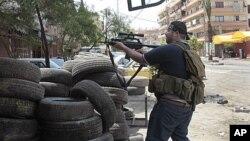 Cuộc chiến ở Syria lan sang Li Băng giữa Hồi giáo Sunni và Alawites. Một tay súng phe Sunni đang chiến đấu trên đường phố ở Tripoli