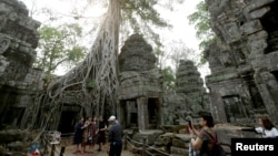 FILE - Tourists visit the Ta Prohm temple complex in Siem Reap province, Cambodia, on March 16, 2019.