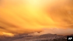 ພາບຂີ້ເຖົ່າໄຟຄວັນກຸ້ມຈາກພູໄຟ Puyehue-Cordon Caulle ຂອງຊີເລ ປົກຄຸມເມືອງ San Martin de Los Andes ໃນປະເທດ Argentina ໃນຍາມຕາເວັນໃກ້ຈະຕົກດິນ, ວັນທີ 14 ມິຖຸນາ 2011.