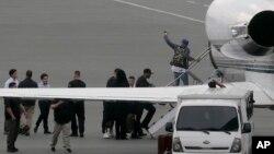 Chris Brown berjalan memasuki pesawat sewaan di Bandara Domestik Manila di kota Pasay, sebelah selatan Manila, Filipina (24/7).