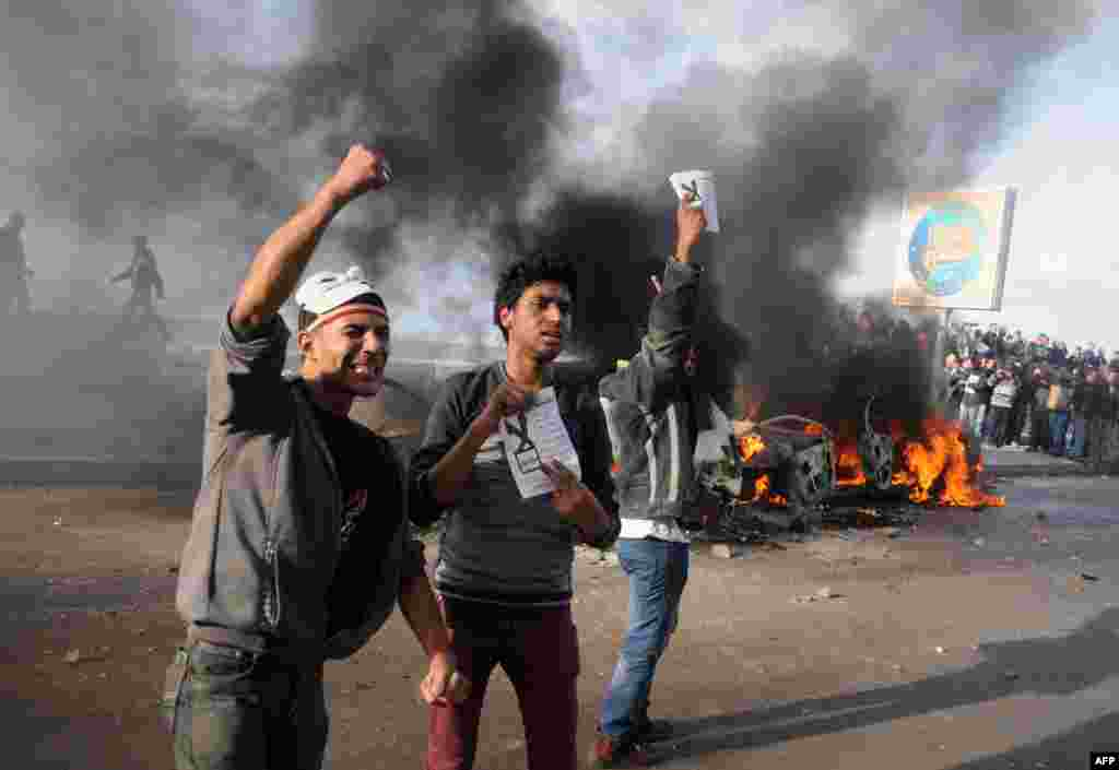 """Egyptian protesters shout slogans in front of burning cars set on fire during a demonstration calling for a """"No"""" vote in a referendum on a new constitution in the coastal city of Alexandria, Dec. 14, 2012."""