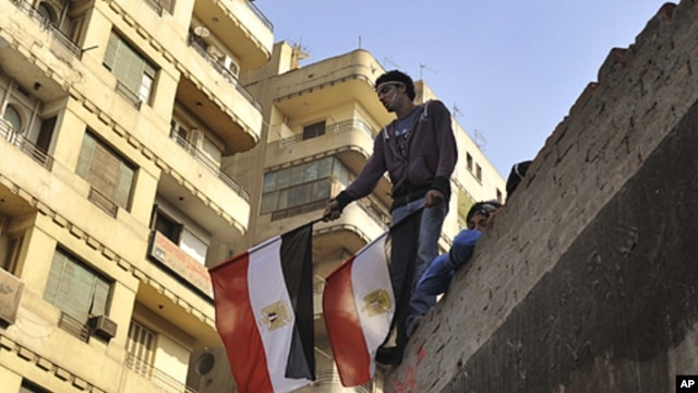 A young Egyptian man holds a national flag while standing on a rooftop between Tahrir Square and the Interior Ministry in Cairo, Egypt, Nov. 26, 2011.