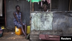 Women sit on the porch of a house in the Congo Town neighborhood of Sierra Leone's capital Freetown, April 28, 2012.