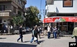 Warga Suriah berjalan di sepanjang pasar terbuka di pusat kota Homs, Suriah, 7 April 2017. (Foto: STRINGER / AFP)