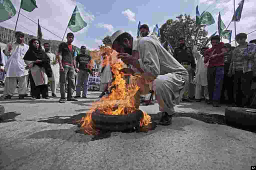 A supporter of the Pakistani religious group Jamaat-e-Islami burns a tire during an anti American rally in Abbottabad, Pakistan, May 6, 2011 (AP).