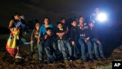 FILE - A group of young migrants from Honduras and El Salvador who crossed the U.S.-Mexico border illegally are stopped in Granjeno, Texas, June 25, 2014.