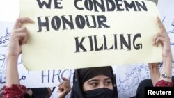 FILE - A Pakistani woman holds a placard during a protest against honor killings in Multan, Oct. 27, 2004.