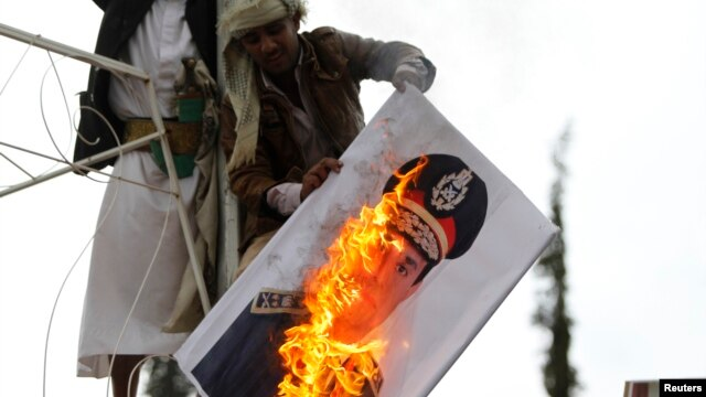 A pro-democracy protester burn an image of Lieutenant- General Abdel Fattah El Sisi, Egypt's Commanding General and Minister of Defense and Military Production, during a demonstration against what they said was a military coup that ousted Egyptian Preside