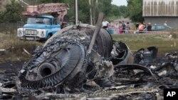Warga lokal melihat puing-puing pesawat Malaysia MH17 yang jatuh ditembak rudal di dekat desa Rozsypne, Ukraina. Keseluruhan 298 penumpang pesawat itu tewas.