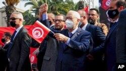Leader of Tunisia's Islamist Ennahda party House Speaker Rached Ghannouchi waves a Tunisian flag during a rally in Tunis, Tunisia, Feb. 27, 2021.