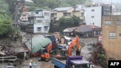 Mangled houses and other debris swept away by a landslide are seen by a road following days of heavy rain in the Izusan area of Atami in Shizuoka Prefecture on July 4, 2021.