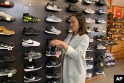 Jennifer Lee, whose family owns Footprint shoe store in San Francisco, stands by a wall of athletic shoes, Aug. 28, 2019. Many of the shoes are made in China and will be subject to new U.S. tariffs on Chinese goods starting Sept. 1.