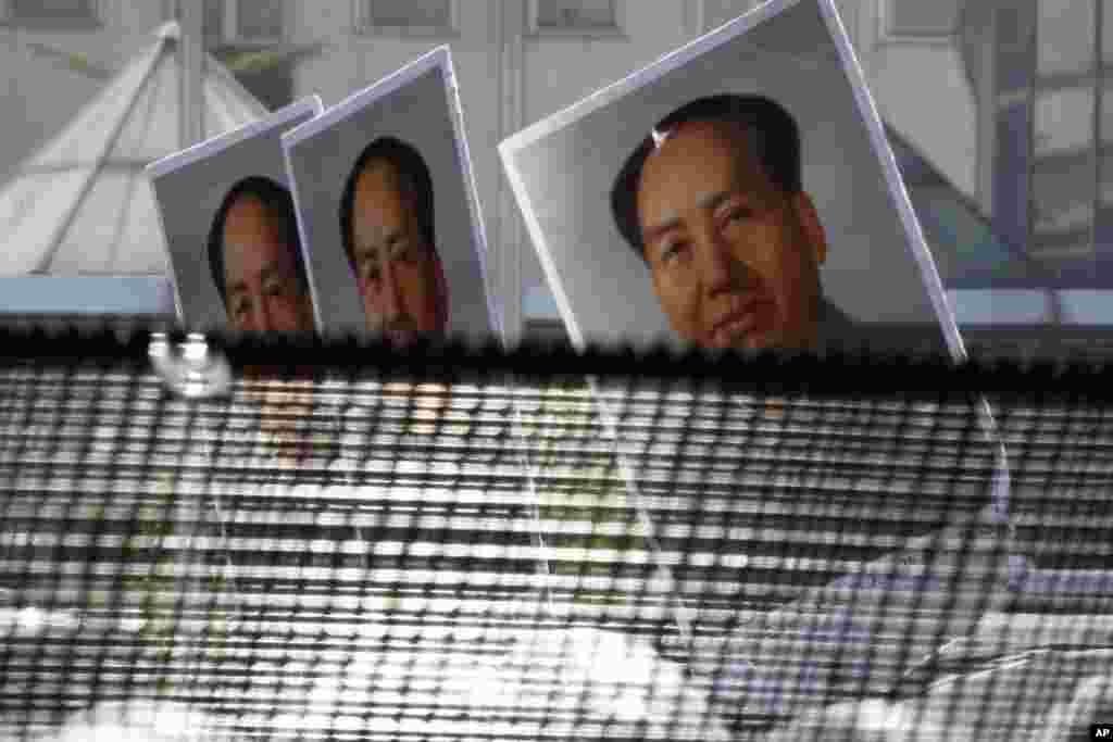 ພວກປະທ້ວງຕໍ່ຕ້ານຍີ່ປຸ່ນ ພາກັນຖືຮູບຂອງມື້ລາງຜູ້ນໍາຄອມມິວນິສ ທ່ານ Mao Zedong ຂະນະທີ່ພາກັນ ເດີນຂະບວນຢູ່ອ້ອມແອ້ມສະຖານທູດຍີ່ປຸ່ນ ໃນນະຄອນຫລວງປັກກິ່ງ, ວັນທີ 16 ກັນຍາ 2012.