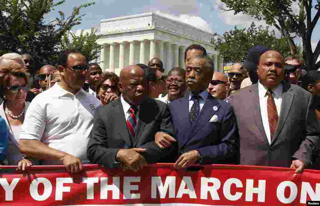 Rev. Al Sharpton (2nd R) links arms with Rep. John Lewis (D-GA) next to Martin Luther King III (R) as they begin to march during the 50th anniversary of the 1963 March on Washington for Jobs and Freedom at the Lincoln Memorial in Washington, Aug. 24, 2013
