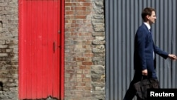 FILE - A man passes a red door and corrugated iron in central London, July 2, 2014. Asylum seekers in the northern English town of Middlesbrough are suffering abuse because they have been housed in properties that almost all have red front doors, making them easy targets for racists.