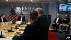 ປະທານາທິບໍດີ ທຣຳ, ຊ້າຍ, ຟັງໃນຂະນະທີ່ ທ່ານແກຣມ (Graham), ຜູ້ອຳນວຍການ ອົງການ NOAA's National Hurricane Center,ຢູ່ໃນຈໍໂລລະພາບ, ລາຍງານຄວາມຄືບໜ້າ ໃນລະຫວ່າງ ກອງປະຊຸມແຈ້ງໃຫ້ຊາບໂດຍຫຍໍ້ ກ່ຽວກັບ ພາຍຸເຮີຣິເຄນໂດຣຽນ ຢູ່ທີ່ Federal Emergency Management Agency (FEMA), ວັນອາທິດ ທີ 1 ກັນຍາ 2019.