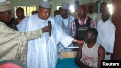Borno State Governor Kashim Shettima, center, visits injured victims of heavy fighting at a hospital in Baga, Nigeria, April 21, 2013.