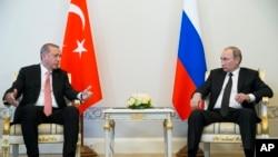 Presiden Turki Recep Tayyip Erdogan (kiri) dan Presiden Rusia Vladimir Putin berbincang dalam pertemuan di St. Petersburg, Rusia Selasa (9/8).