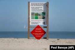 A warning sign against algae bloomsstands on an empty Maumee Bay State Park public beach on Lake Erie in Oregon, Ohio, on Friday, September. 15, 2017.