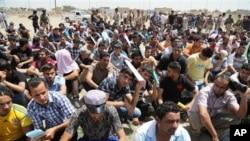 Pria-pria Irak berkumpul di pusat perekrutan angkatan darat di Baghdad untuk menjadi anggota militer sukarela melawan pemberontak (14/6). (AP/Karim Kadim)