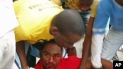 Manifestante espancado pela polícia, socorrido em plena via pública durante uma manifestação no ano passado (Arquivo VOA)