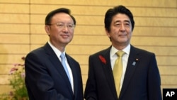 中国国务委员杨洁篪(左)访问日本与日本首相安倍晋三握手。